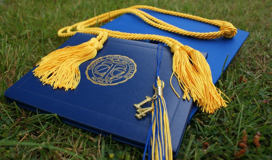 Canva - Diploma and Square Academic Hat on Grass Field